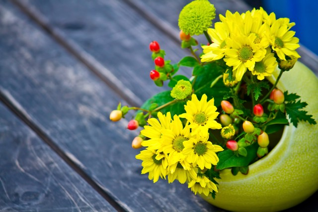 丸い花瓶の黄色い花の写真