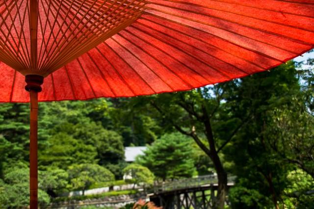 日本庭園と赤い日傘の写真