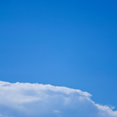 「青空とベンチに座る青年」の写真素材