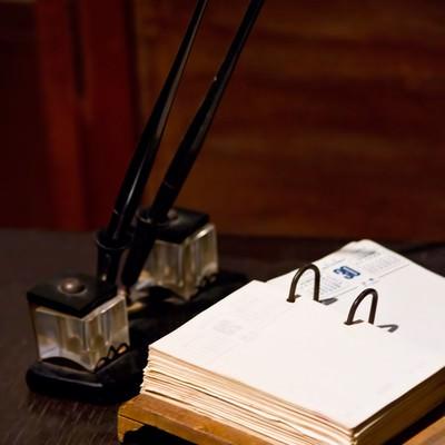 古いデスクのペンとメモの写真