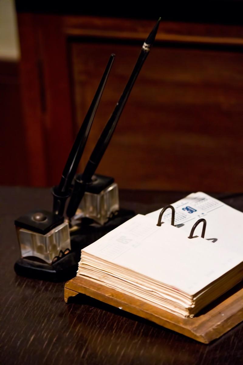 「古いデスクのペンとメモ」の写真