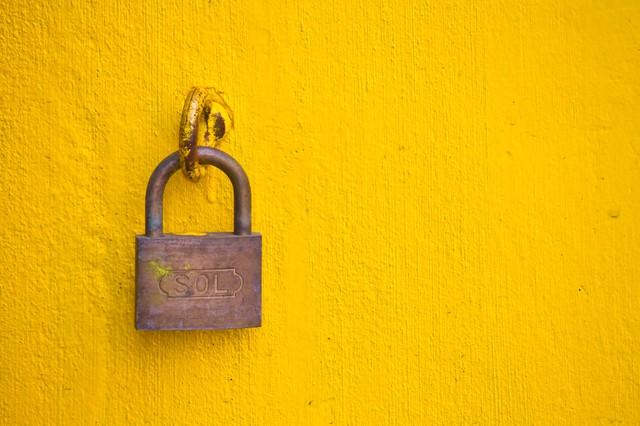 黄色い壁と南京錠の写真