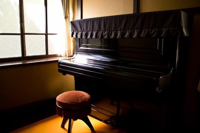 窓際の古いピアノの写真