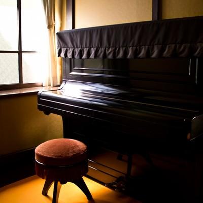 「窓際の古いピアノ」の写真素材