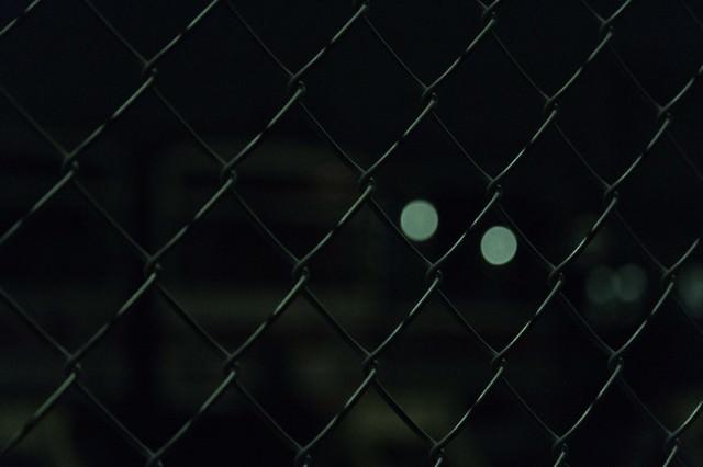 夜の金網越しの写真