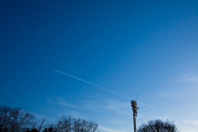 青空に伸びる飛行機雲の写真