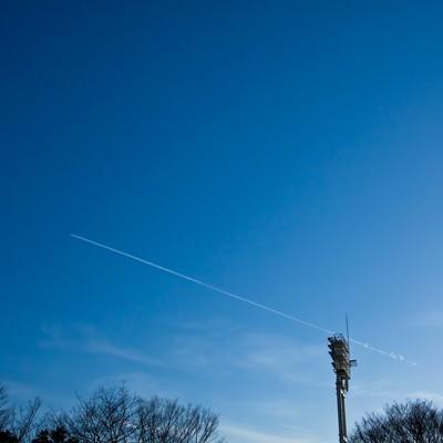 「青空に伸びる飛行機雲」の写真素材