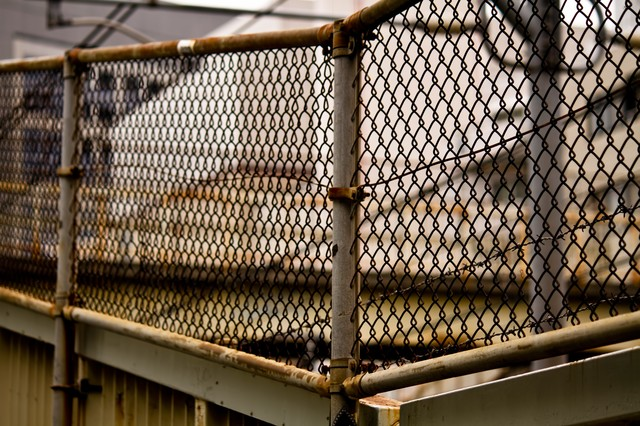 錆びた金網のフェンスの写真