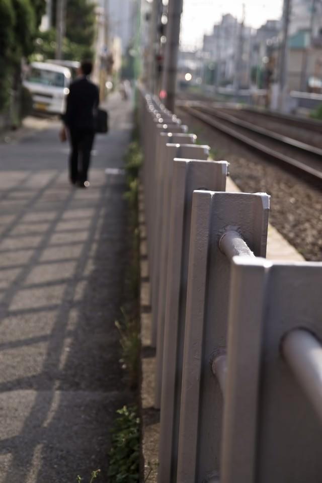 線路沿いを歩くサラリーマンの写真