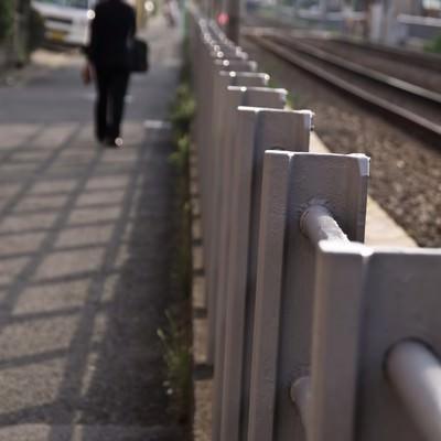 「線路沿いを歩くサラリーマン」の写真素材