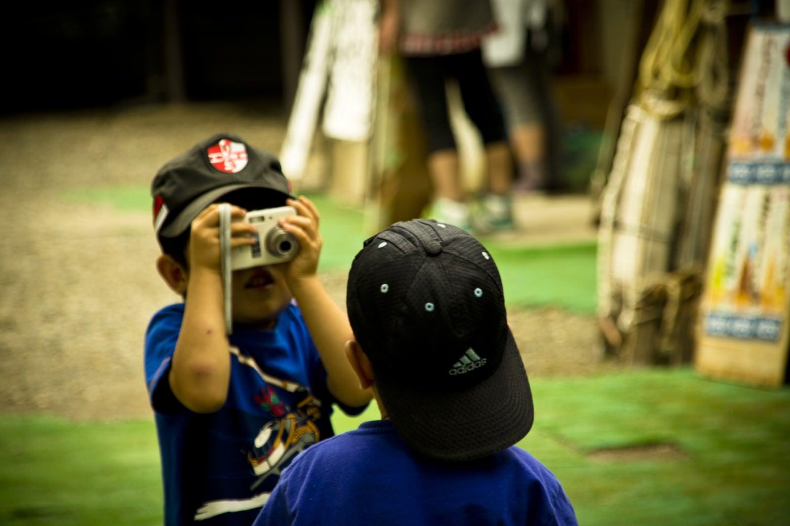 「写真を撮り合う子供の兄弟」