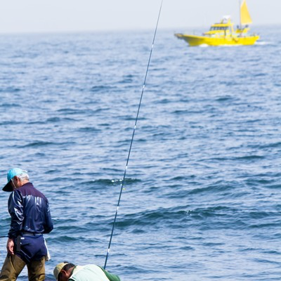 「岩場の釣り人と船」の写真素材