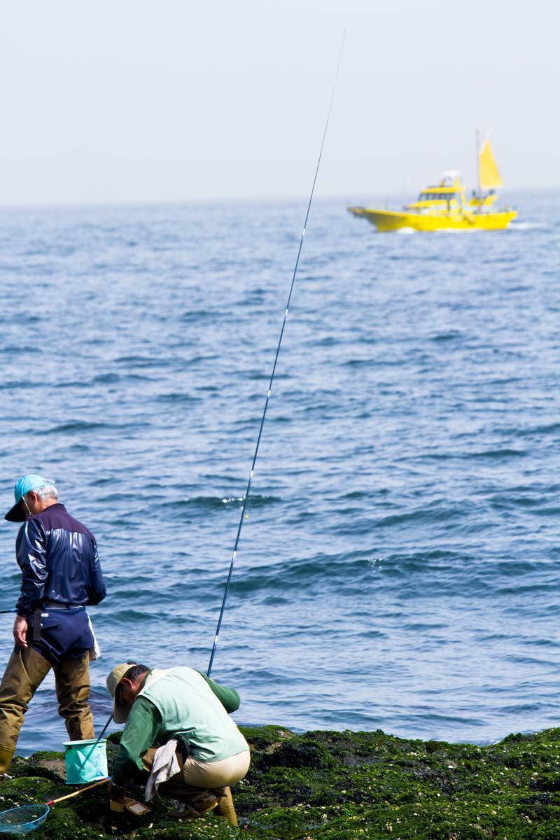 「岩場の釣り人と船」の写真