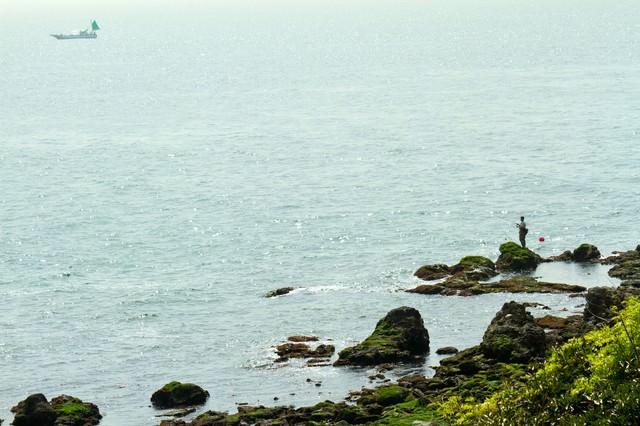 岩場の釣り人の写真