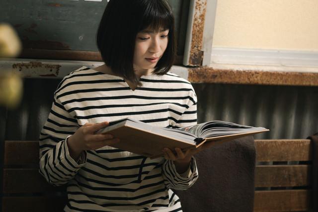 カフェで写真集を眺める女性の写真