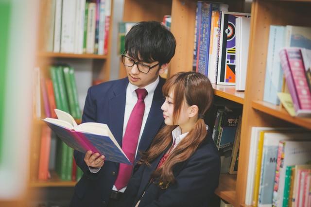 図書室でデートをする倹約家カップルの写真