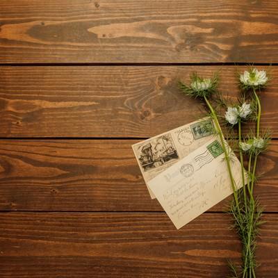 「机に置かれた手紙と花」の写真素材