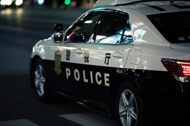 警察車両に映る夜のネオンの写真