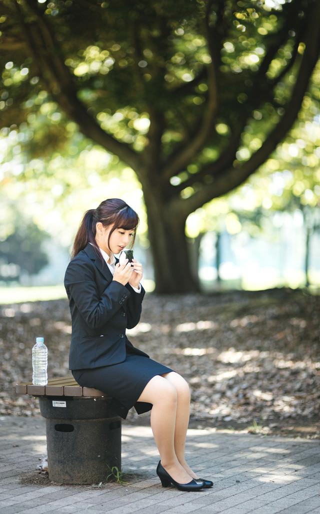 公園でぼっち飯するリクルーガールの写真