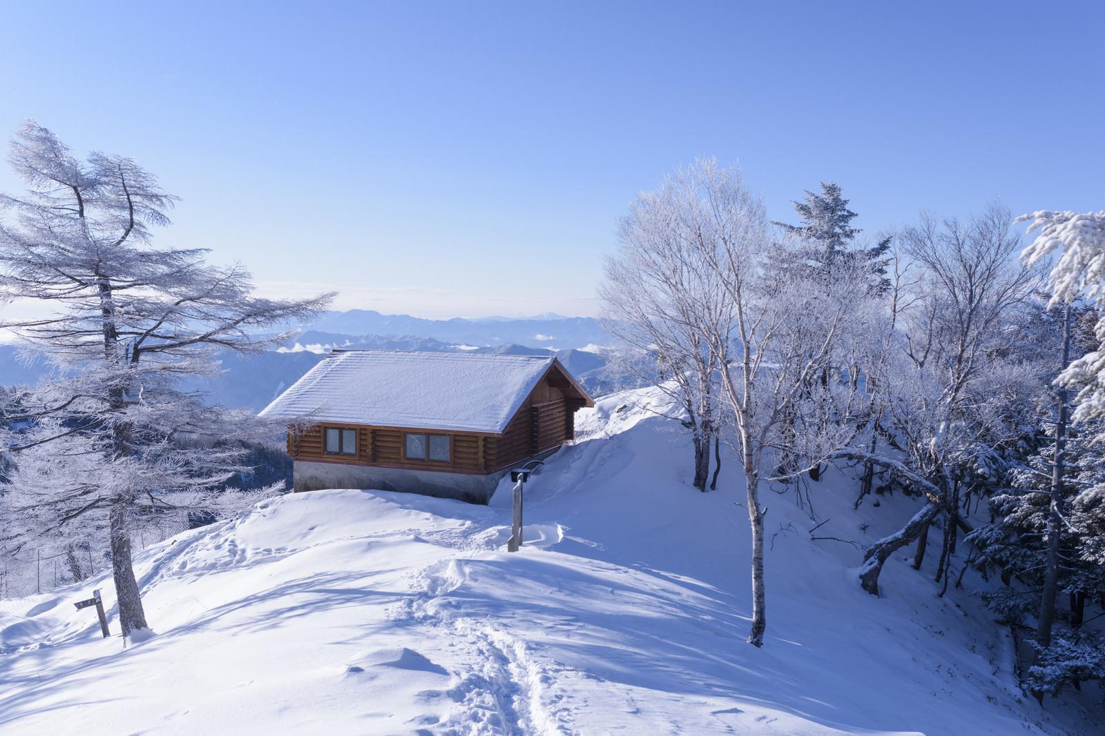 「雪に包まれた雲取山山頂と雲取山避難小屋」の写真