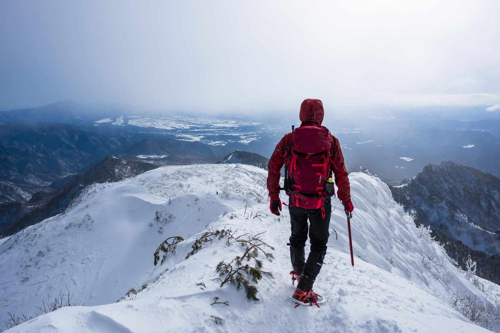「上州武尊山の稜線を歩く赤い登山者」の写真