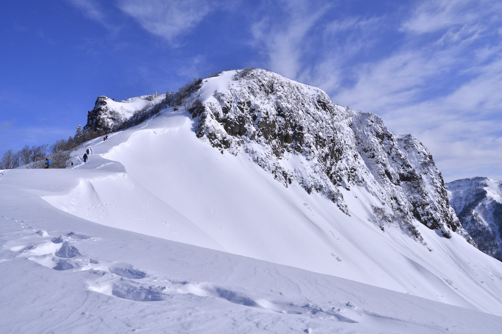 「冬の断崖絶壁に挑む登山者と足跡」の写真