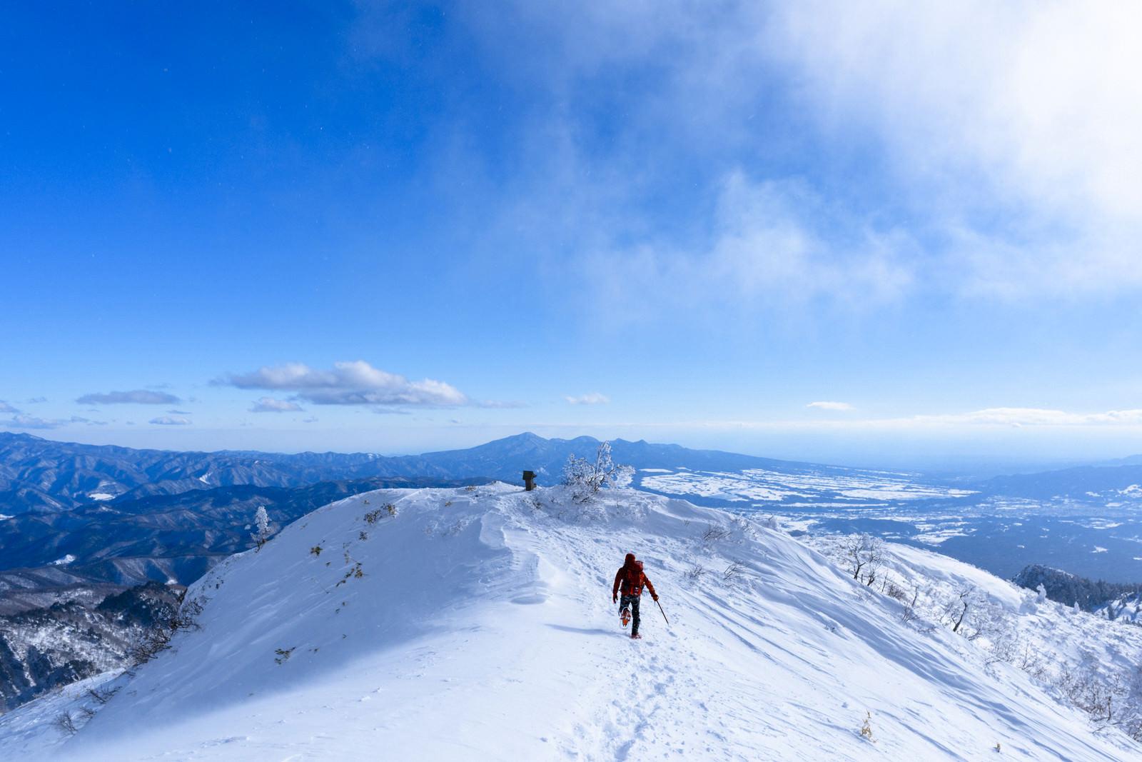 「雪原で駆け出す登山者(上州武尊山)」の写真