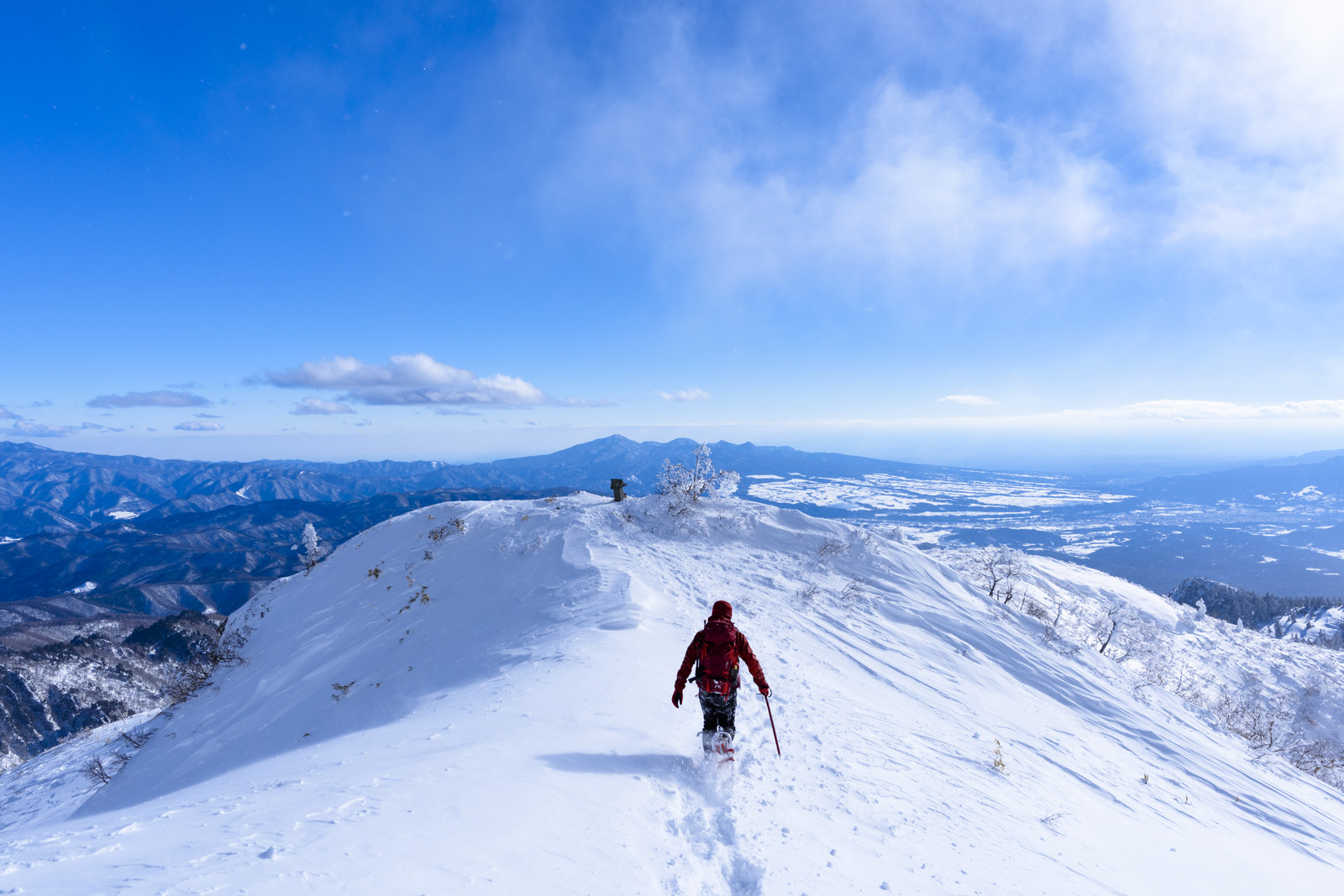 「雪原を走る赤い登山者(上州武尊山)」の写真