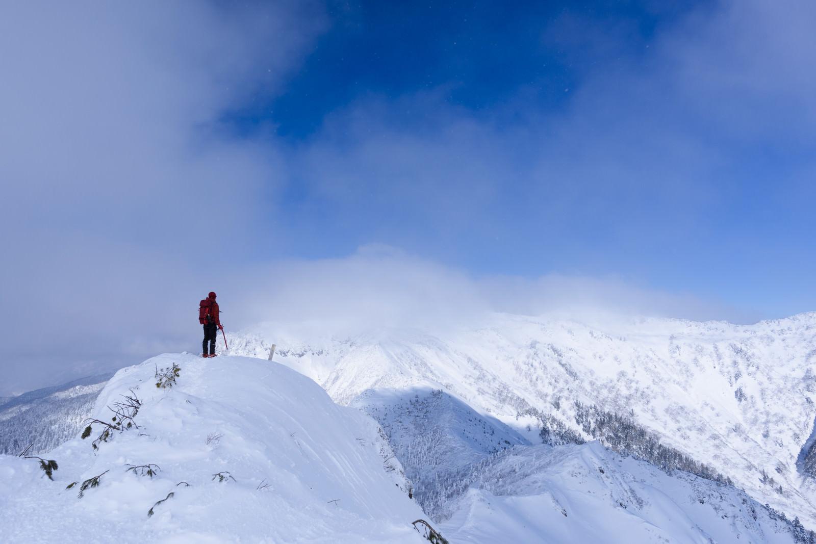 「冬の上州武尊山を拝む登山者」の写真