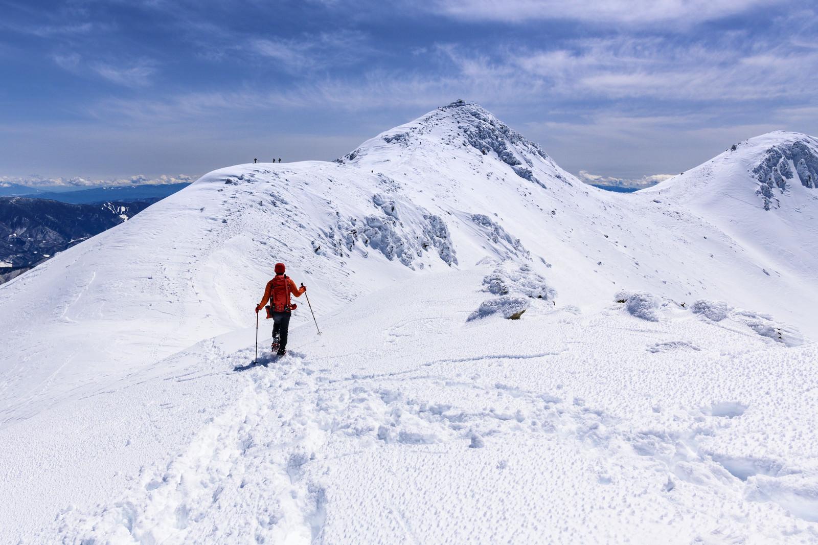「冬の乗鞍岳を登る赤い登山者」の写真