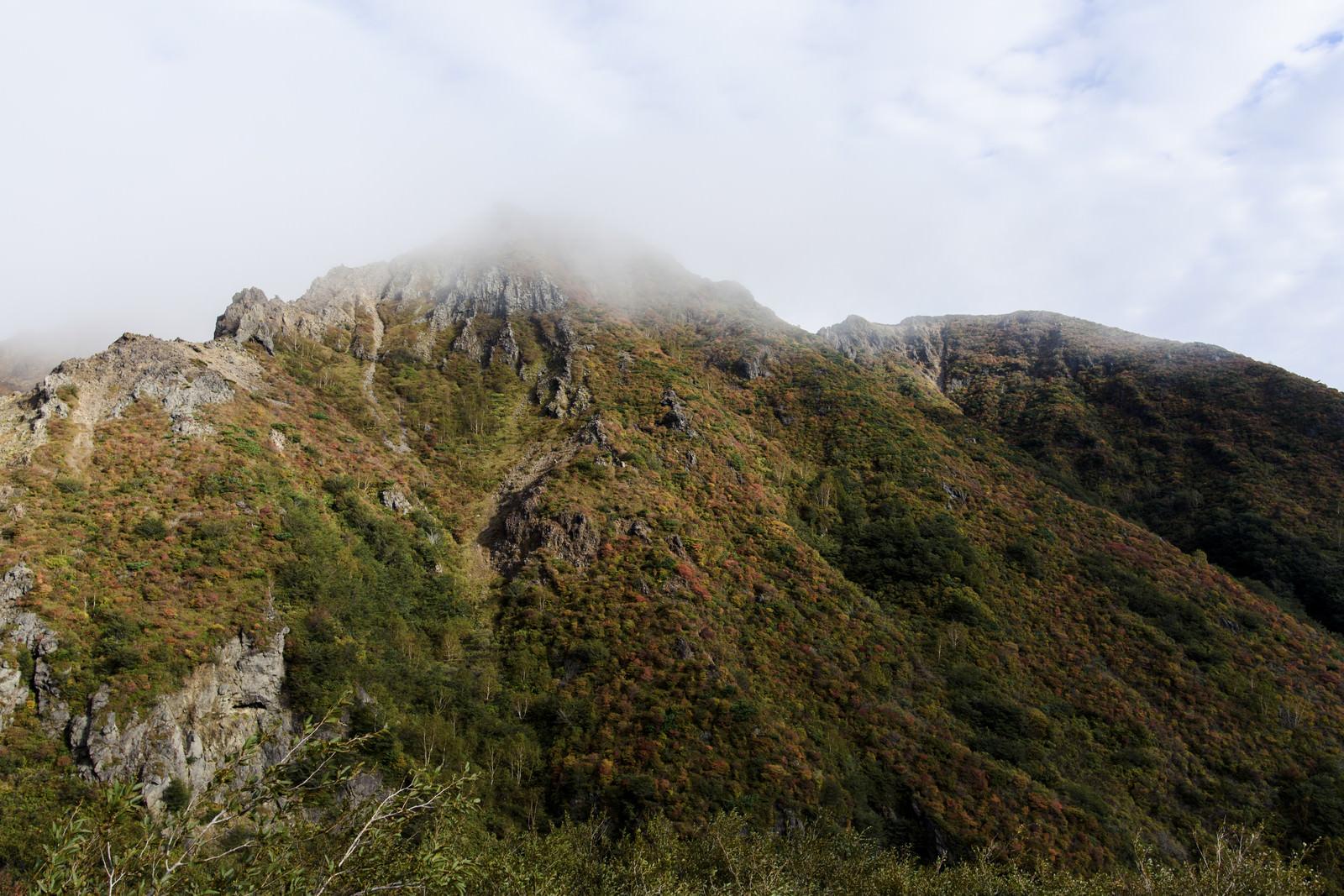 「雲に包まれる紅葉した那須朝日岳(あさひだけ)」の写真
