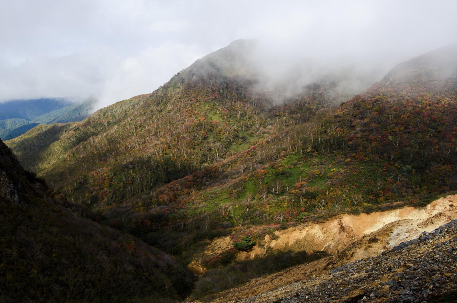 「雲の隙間から紅葉をのぞかせる那須岳(なすだけ)」の写真
