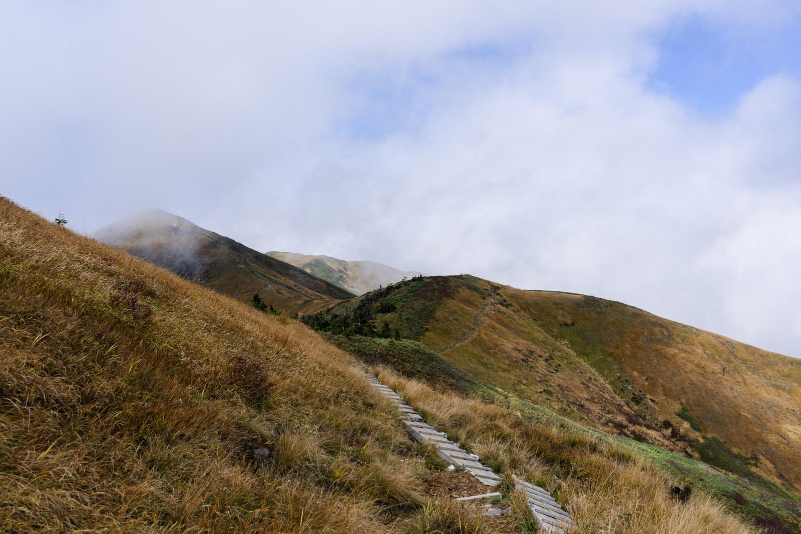 「雲が飛び交う紅葉の巻機山稜線」の写真