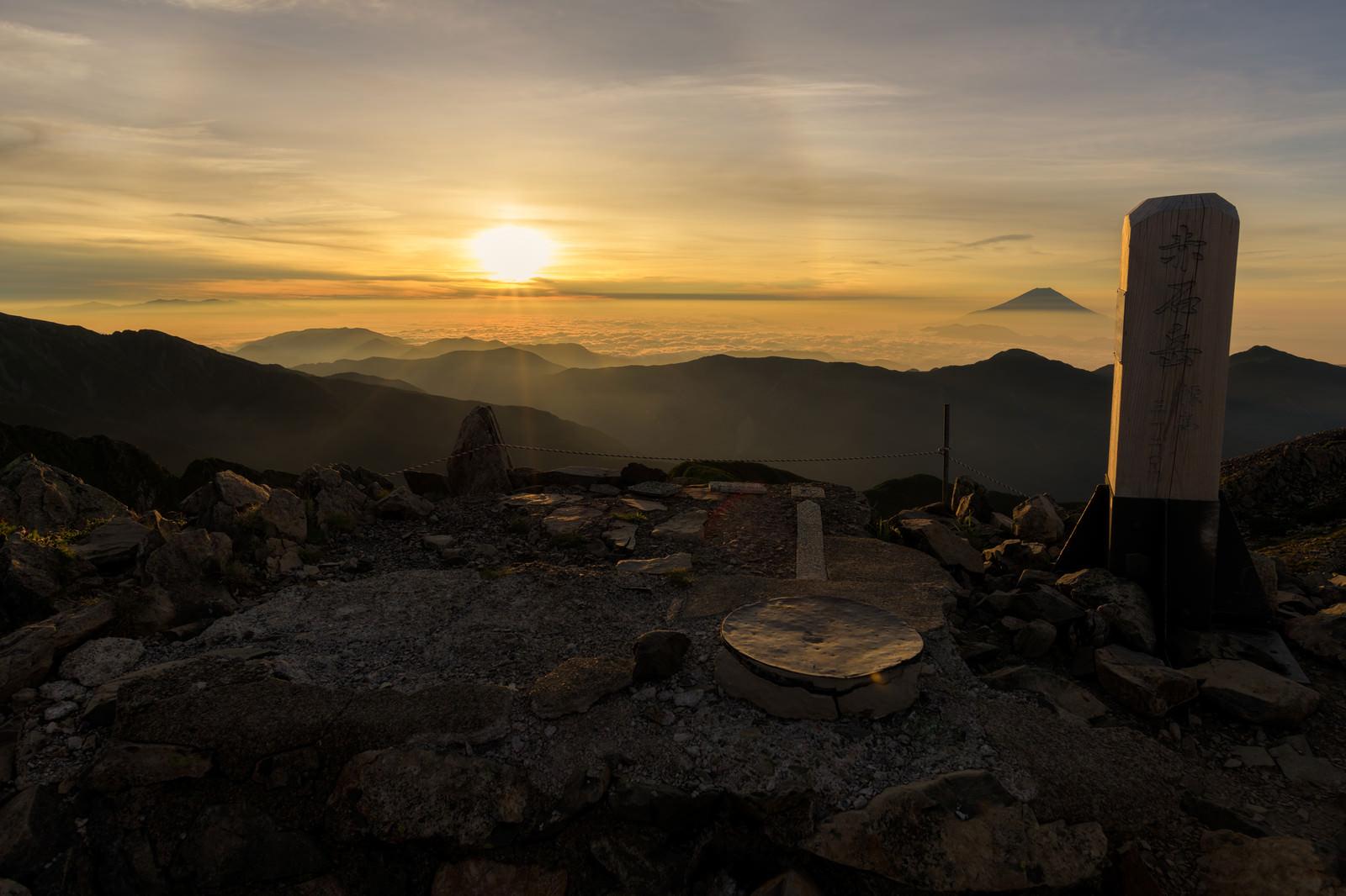 「朝日に照らされる赤石岳山頂碑(南アルプス)」の写真