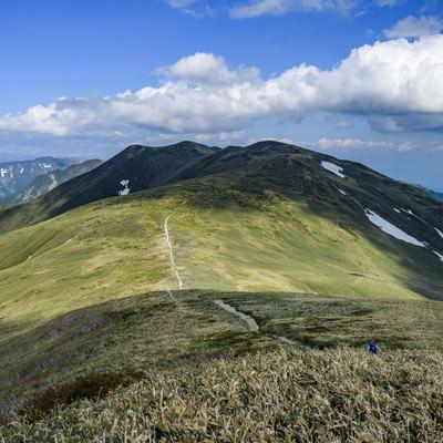 晴れ間に照らされる仙ノ倉山の稜線と登山道の写真