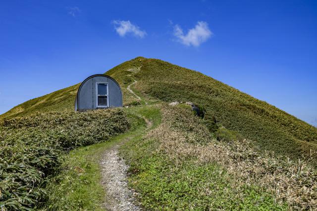避難小屋と山頂へと続く登山道(谷川岳)の写真