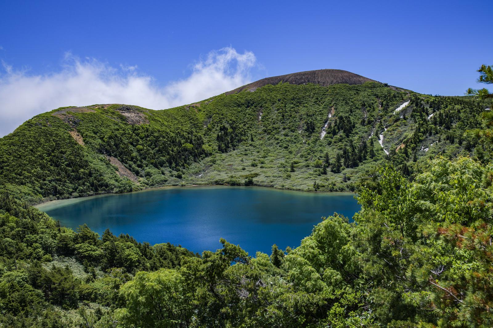 「登山道の茂みから見るカルデラ湖(魔女の瞳)」の写真