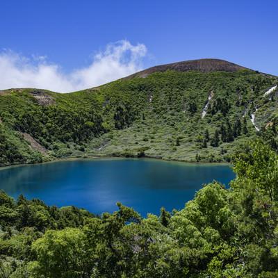 登山道の茂みから見るカルデラ湖(魔女の瞳)の写真