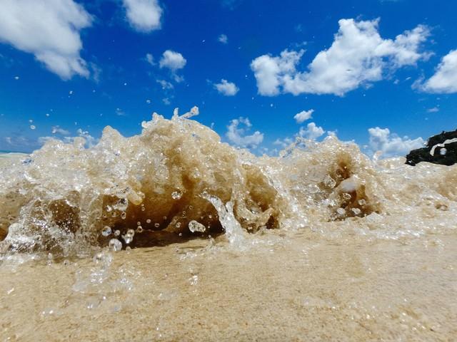 砂浜に打ち上げるさざ波と水しぶきの写真