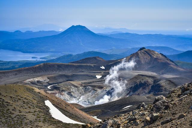 噴煙吹き上げる雌阿寒岳と雄阿寒岳の写真