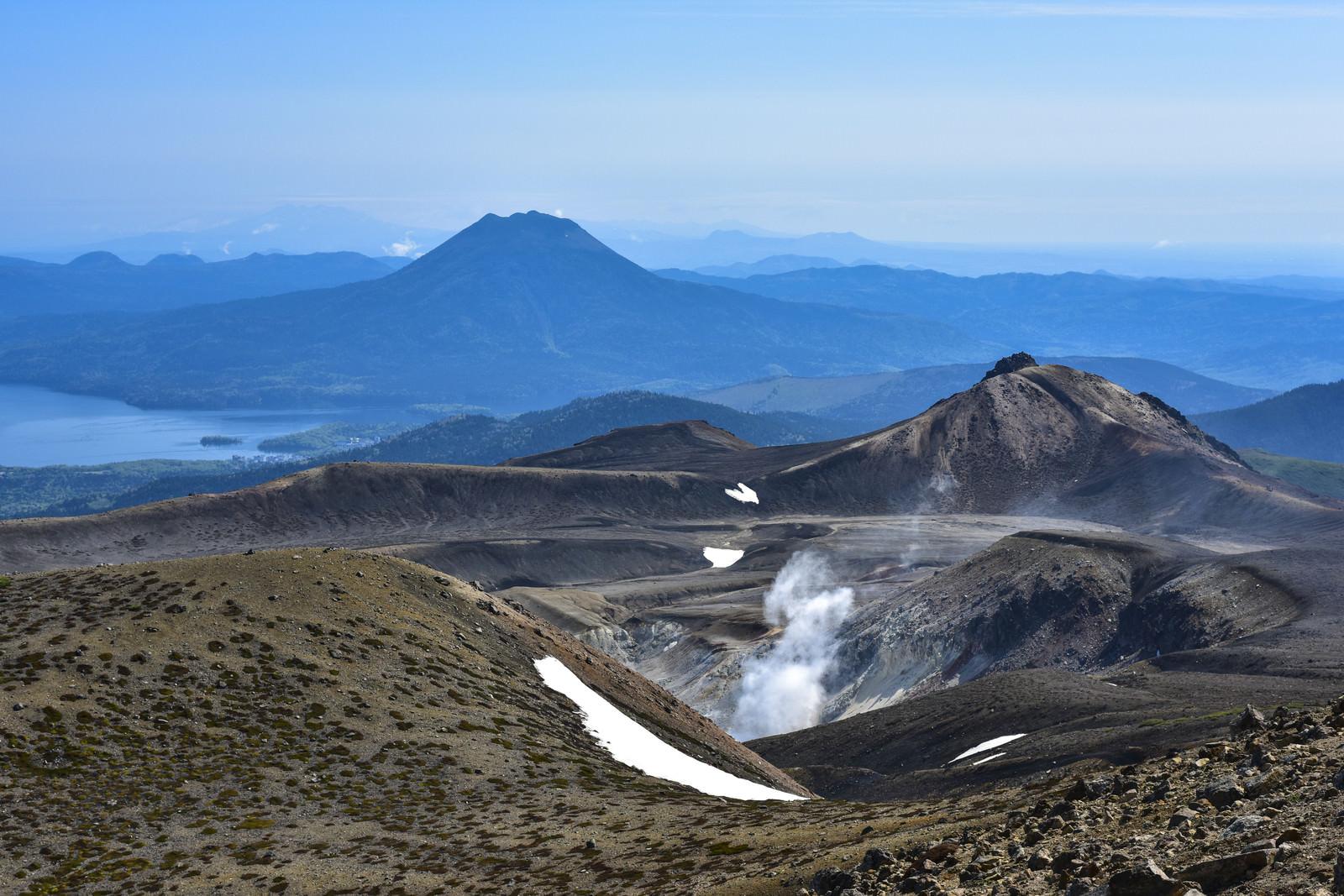 「火山から沸き立つ蒸気と雄阿寒岳(北海道釧路市)」の写真