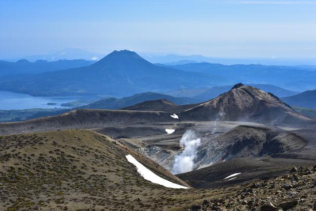 火山から沸き立つ蒸気と雄阿寒岳(北海道釧路市)の写真
