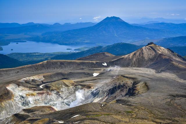 噴煙をあげる火口と阿寒湖周辺を一望する景色の写真