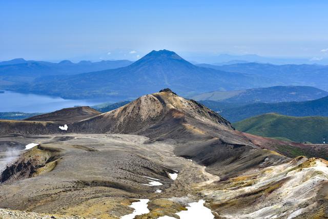 雪が残る雄阿寒岳の写真