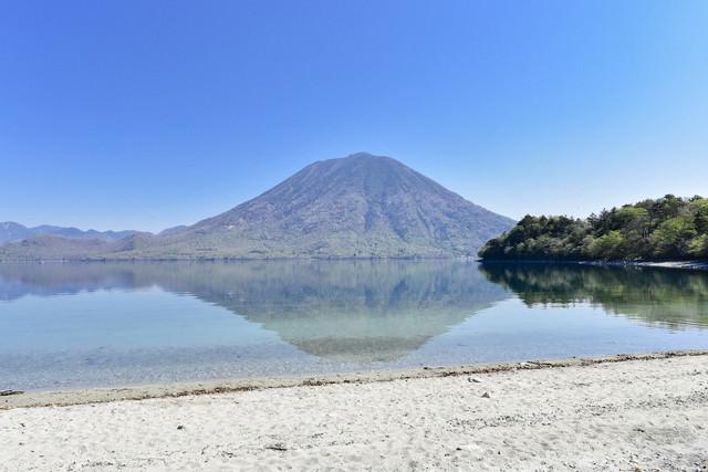 砂浜の向こうに浮かぶ男体山(栃木県日光市)の写真