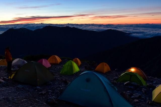 ご来光を待つテントたちと雲海の写真