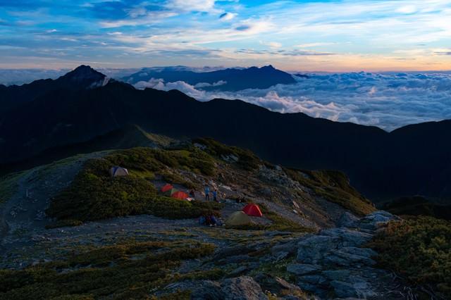 南アルプスの壮大な夜明けを楽しむ登山者の写真