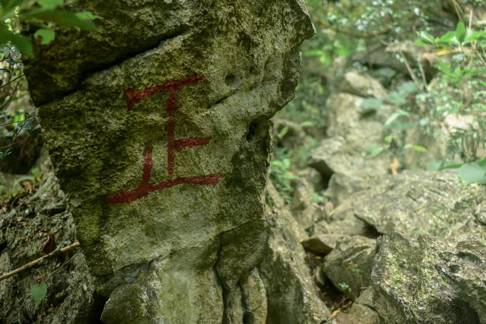 「登山道の岩壁に描かれた赤い正の字」の写真