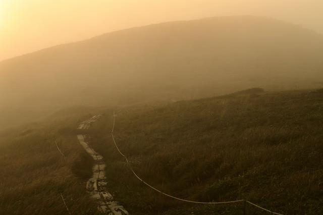 ガスに包まれる夕暮れの登山道の写真