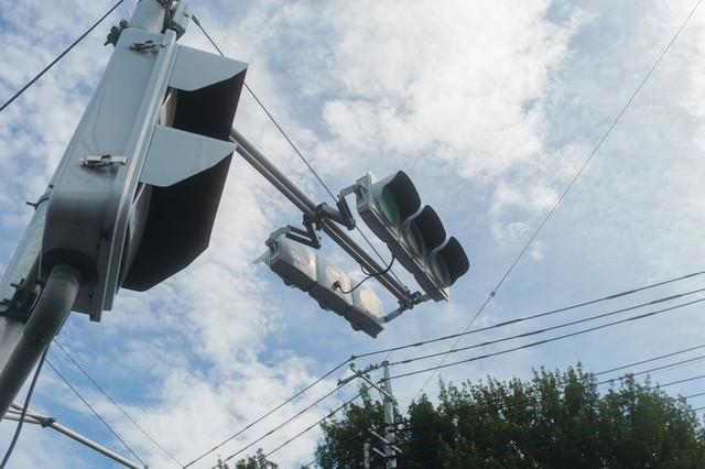 歩道から見上げる信号機の写真